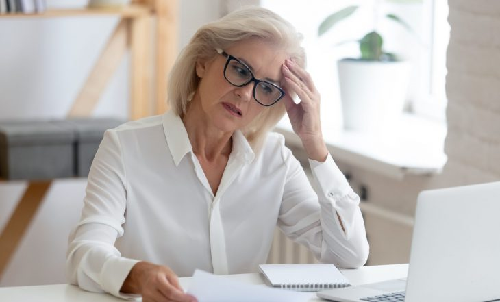 Pensive,Aged,Businesswoman,In,Glasses,Sit,At,Office,Desk,Thinking