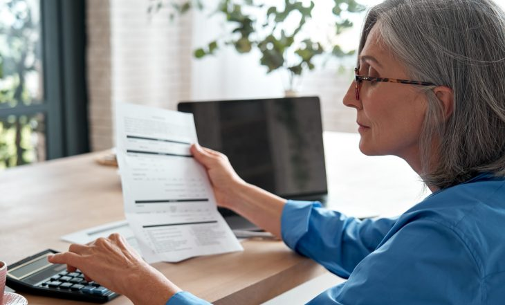 Senior,Mature,Business,Woman,Holding,Paper,Bill,Using,Calculator,,Old