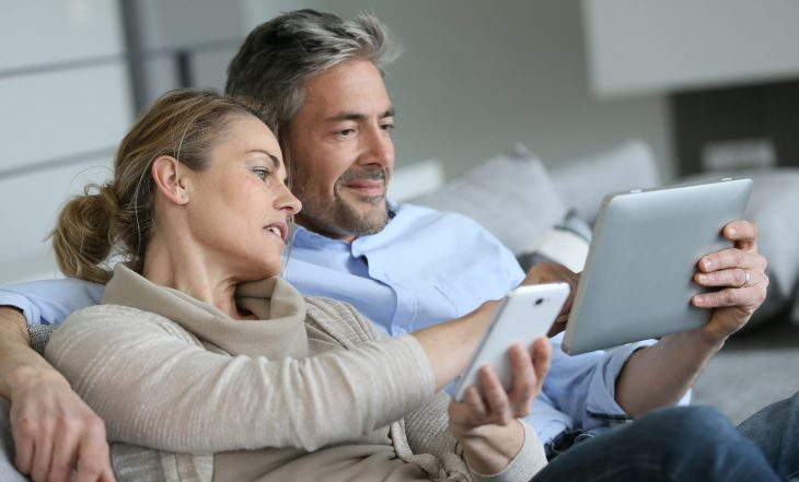 Mature,Couple,At,Home,Using,Smartphone,And,Tablet